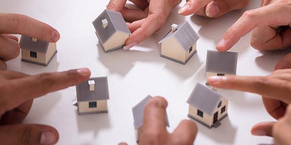 Hände und Häuser als Symbol für Eigentümergemeinschaft